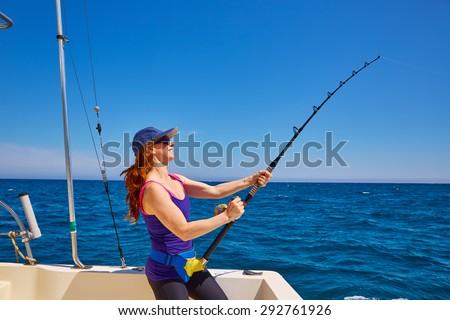 Beautiful woman girl fishing rod trolling in saltwater in a boat trolling