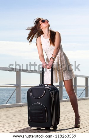 Beautiful woman going on a sea mooring suitcase pier
