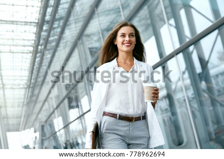 Photo of Beautiful Woman Going To Work With Coffee Walking Near Office Building. Portrait Of Successful Business Woman Holding Cup Of Hot Drink In Hand On Her Way To Work On City Street. High Resolution.