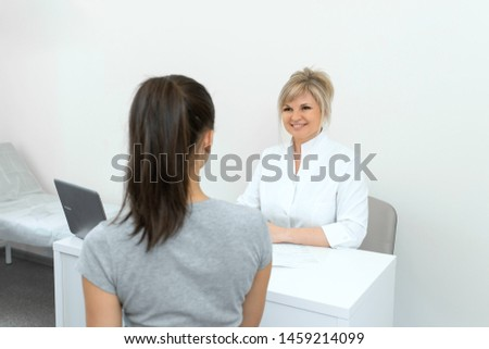 Beautiful woman gynecologist is conducting a reception with a young girl. Consultations and help gynecologist.