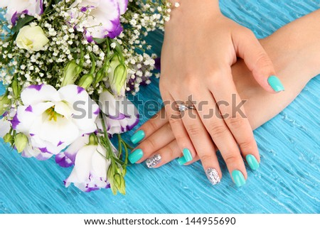 Beautiful woman hands with blue manicure near bouquet of beautiful flowers, on color background