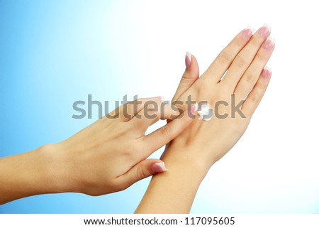 Beautiful woman hands with cream, on blue background - stock photo