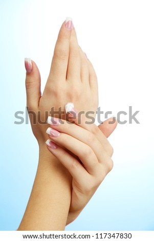 Beautiful woman hands with cream, on blue background