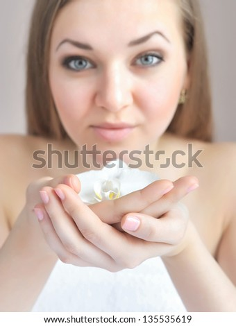 Beautiful woman hands with white orchid flower. Focus is on a hand