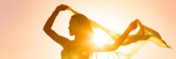 Beautiful woman happy free in sunset glow waving scarf in the wind dancing in sun panoramic banner. Silhouette feminine lady freedom for wellness and healthy living.