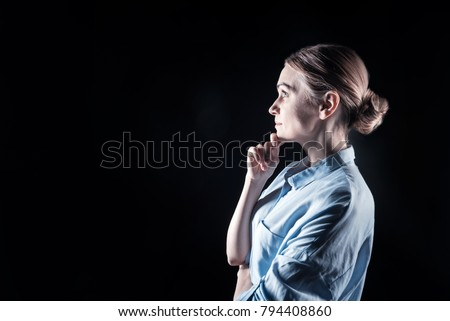 Beautiful woman. Happy nice thoughtful woman standing half face an holding her chin while looking in front of her