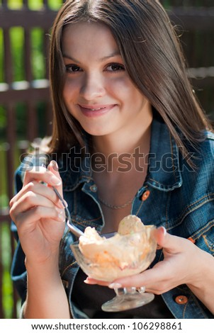 Beautiful woman happy smiling sitting in cafe and eating ice cream from glass bowl