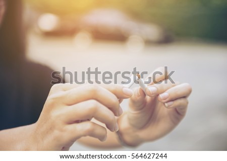 Beautiful woman happy to breaking a cigarette, quit smoking concept,