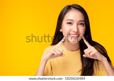 Beautiful woman has beautiful tooth, white teeth, nice tooth alignment. Pretty girl show her teeth. Asian female get beauty braces. Attractive lady get confidence copy space, yellow background
