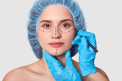 Beautiful woman has marked arrows under eyes. Lady wants to improve her appearance. Plastic surgeon with blue gloves draws black lines before face lifting. Female with medical cap against grey wall.