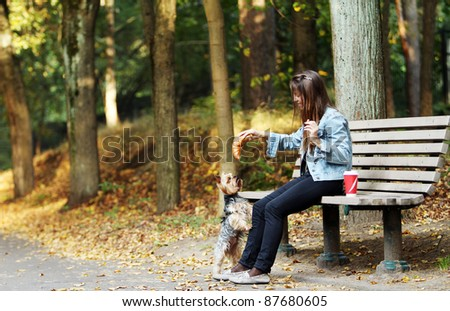 Beautiful woman have lunch while strolling with her dog in the park