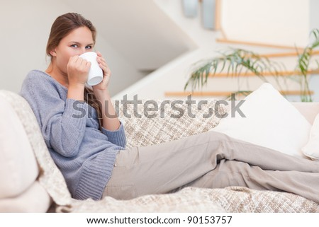 Beautiful woman having a cup of tea in her living room