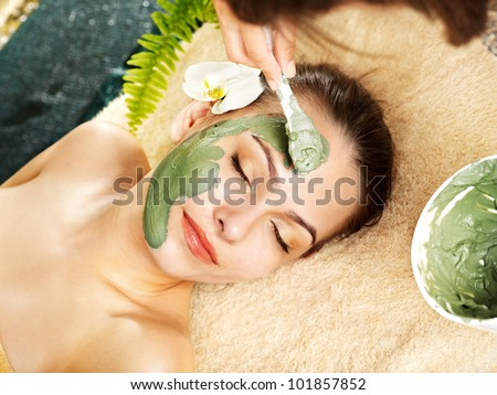 Beautiful woman having clay facial mask apply by beautician