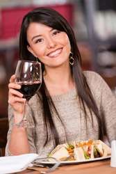 Beautiful woman having dinner at a restaurant and drinking wine