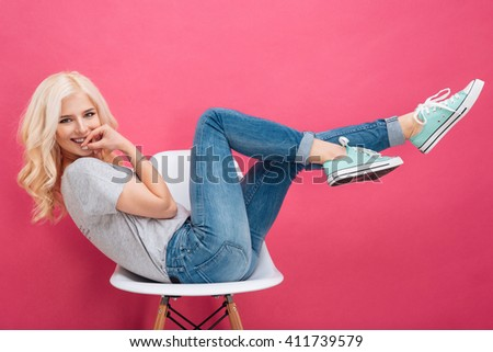 Beautiful woman having fun on the chair over pink background