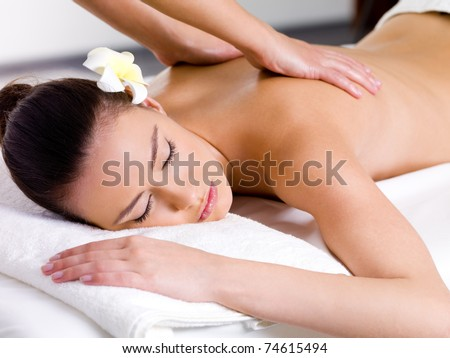 Beautiful woman having relaxing massage on her back in spa salon