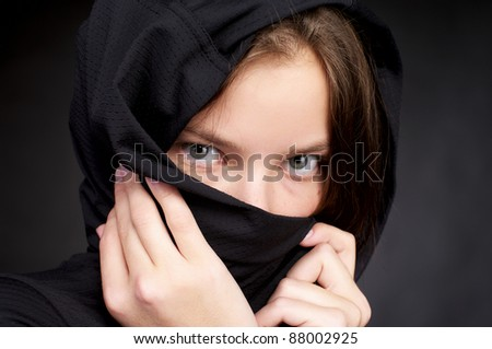 Beautiful woman hiding her face by black headscarf