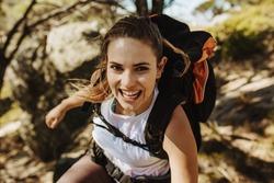 Beautiful woman hiking mountain. Female mountaineer having fun while climbing a mountain with a backpack.