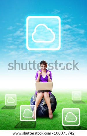 Beautiful woman hold notebook computer and present the Cloud icon on the blue sky and grass field : Elements of this image furnished by NASA