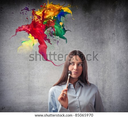 Beautiful woman holding a paintbrush with colors coming out from it