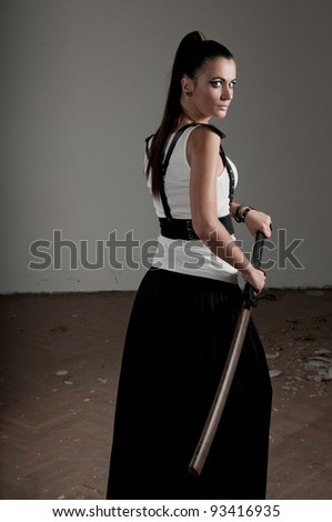 Beautiful woman holding a sheathed sword looking back