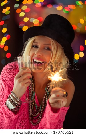 Beautiful woman holding a sparkler and a glass of champagne while having fun on a New Year's Eve.