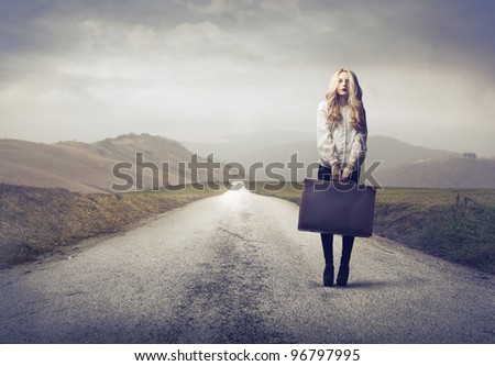 Beautiful woman holding a suitcase on a countryside road