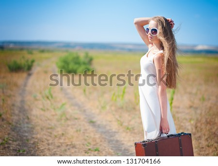 Beautiful Woman holding a suitcase standing on a road #131704166