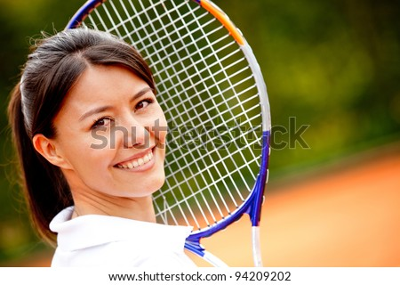 Beautiful woman holding a tennis racket at the court and smiling