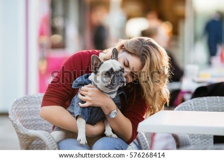Beautiful woman holding adorable fawn french bulldog in her lap in cafeteria.