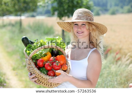 Beautiful woman holding basket of fresh vegetables