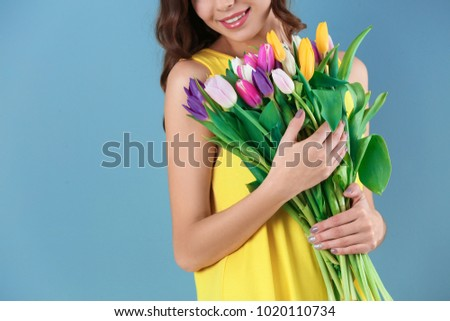 Beautiful woman holding bouquet of tulips on color background #1020110734