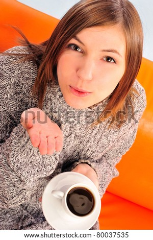 Beautiful woman holding cup of black coffee sitting on couch wearing warm sweater. Sending air kiss to camera - stock photo