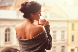 Beautiful woman holding cup of coffee standing on the balcony. Fascinated by the aroma of coffee