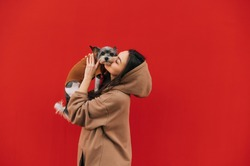 Beautiful woman holding cute biewer terrier dog in her arms and kissing, pet looking at camera, isolated on red background. Lady stands with a dog on a background of a red wall.