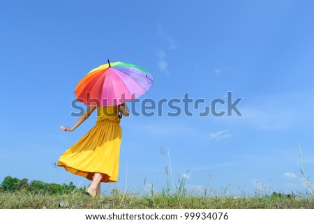 Beautiful woman holding multicolored umbrella and blue sky
