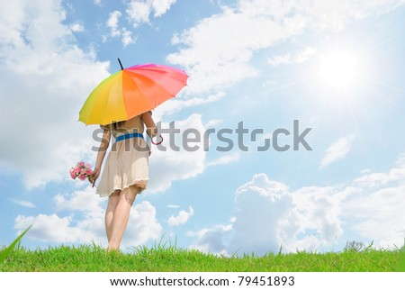 Beautiful woman holding multicolored umbrella and cloud sky