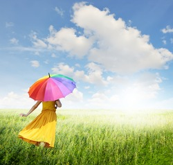 Beautiful woman holding multicolored umbrella in green grass field and cloud sky