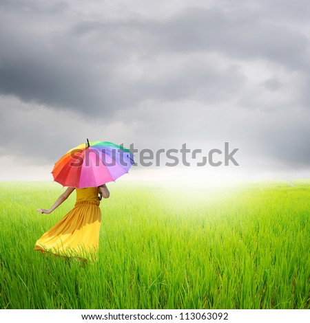 Beautiful woman holding multicolored umbrella in green rice field and rainclouds