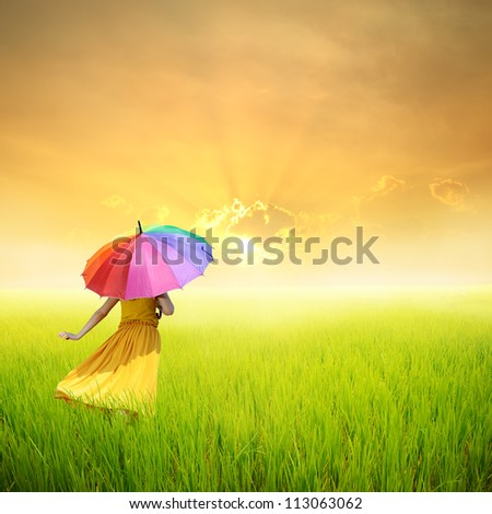 Beautiful woman holding multicolored umbrella in green rice field and sunset