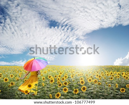 Beautiful woman holding multicolored umbrella in sunflower field and cloud sky
