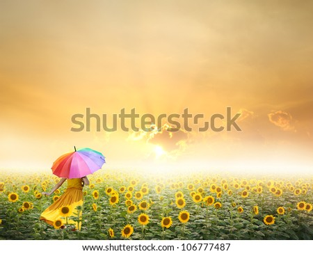 Beautiful woman holding multicolored umbrella in sunflower field and sunset