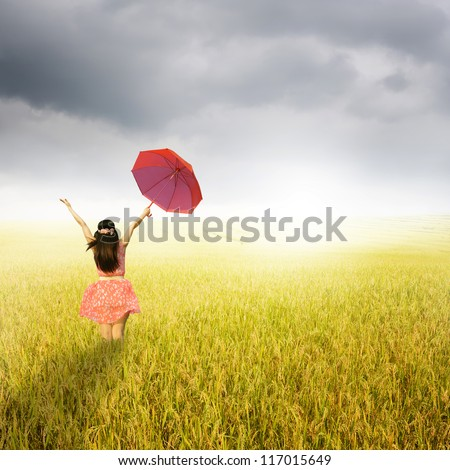 Beautiful woman holding red umbrella in rice field and rainclouds