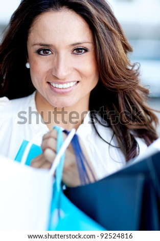 Beautiful woman holding shopping bags and smiling
