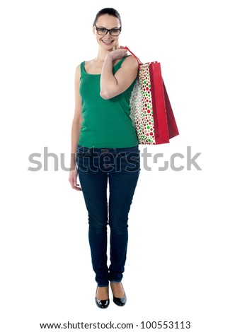 Beautiful woman holding shopping bags on her shoulders, smiling at camera