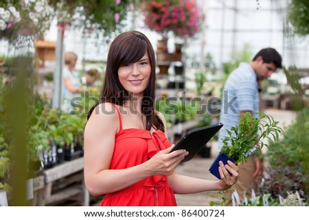 Beautiful woman holding tablet and potted plant with people in background