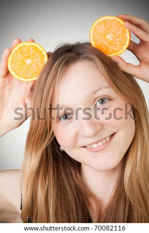 Beautiful woman holding two halfs of orange on her head like Mickey Mouse ears