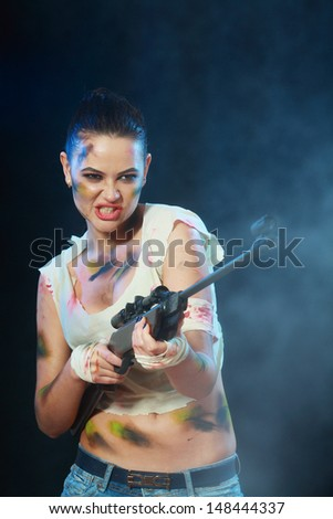 Beautiful woman holding weapon weared camo over dark background