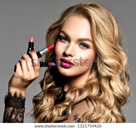 Beautiful woman holds  lipsticks. Makeup. Beauty concept. Pretty girl with long curly hair.  Fashion make-up.  Closeup portrait. Gorgeous face of an attractive fashion model. Bright red lips. #1321754426