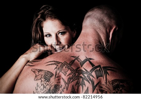 Beautiful Woman hugging and looking over the shoulder of a man